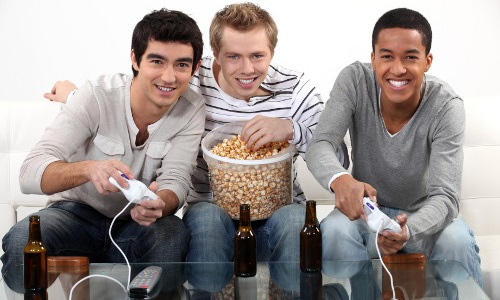 Three friends playing video games while drinking beer and one of them looks slightly sad on the inside.